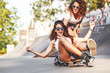 canvas print picture - Two female friends playing with skateboard.One girl pushing other from behind.Laughing and fun.