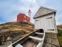 Old Lighthouse With Decrepit Shed And Old Boat