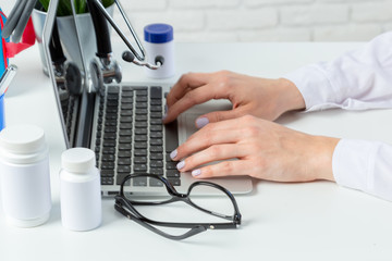 Female doctor is typing in laptop computer
