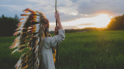 Little girl playing outdoors in the field, wearing Indian headdress, pretending to be a native American. Watching beautiful sunset