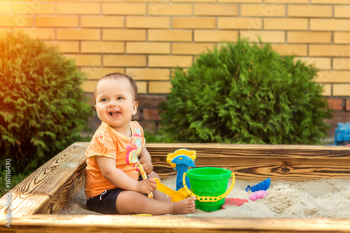 Fotografie, Obraz  Happy little girl playing in a sandbox on the playground