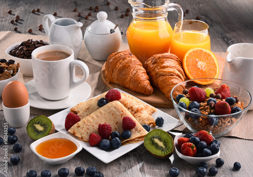 Fototapeta  Breakfast served with coffee, juice, croissants and fruits