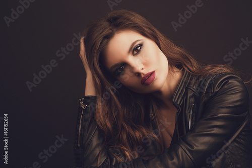 Fotografía  Portrait of the beautiful young woman with wavy brown hair posing at studio over black background