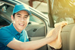Smiling auto service staff cleaning car door