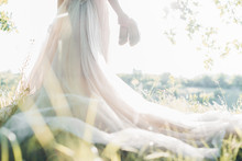 Bride In Wedding Dress Holds Shoes Against Sun. Fine Art Photography