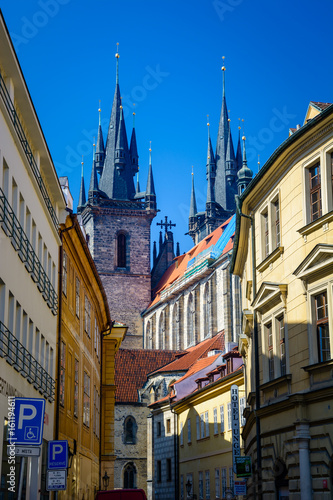 The Church of our Lady before Tyn from an intersting perspective as seen from a sidewalk with colorful buildings on both sides Poster