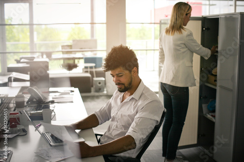 Fototapety, obrazy: Business people in office. African business man reading document Caucasian woman looking for document.
