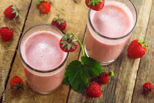 Foto op Plexiglas Milkshake Milkshake made of fresh ripe strawberry on a rustic wooden table. Healthy fruit drink for healthy breakfast. Top view close-up shot.