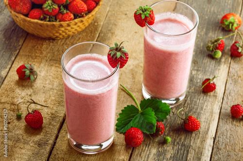 Foto op Plexiglas Milkshake Milkshake made of fresh ripe strawberry on a rustic wooden table. Healthy fruit drink for healthy breakfast.
