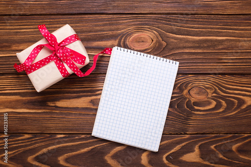 Wrapped box with present and empty tag on aged wooden background.
