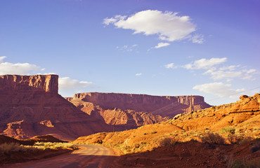 Fototapeta Castle Valley Road Through Golden Desert Mesas and Cliffs at Sunset