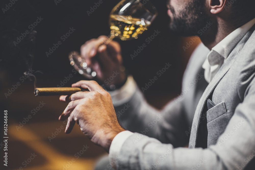 Fototapeta Young man tasting white wine and smoking cigar