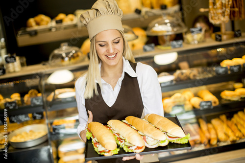 In de dag Bakkerij Beautiful female bakery posing with various types of sandwiches in the baker shop