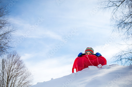 Poster Wintersporten Young boy, outdoors in snow, at top of hill with sled, low angle view