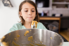 Young Girl Eating Cookie Mix F...