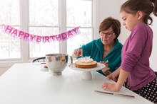 Grandmother And Granddaughter Assembling Layered Birthday  Cake