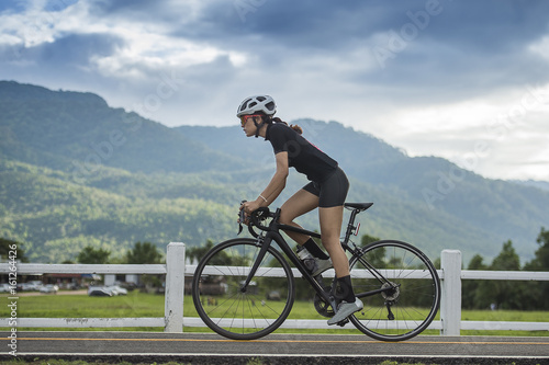 Foto auf Gartenposter Radsport Woman Cyclist riding a Road bike in countryside track with green forest and clear climate ,sport and wellness concept