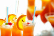 Glasses of Tequila Sunrise cocktail with citrus slices on blurred background, closeup