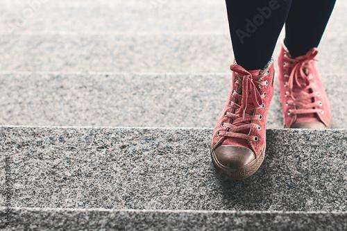 Kobieta iść na piechotę w czarnych leginsach i różowych sneakers wspina się kamiennych schodki plenerowych z kopii przestrzenią