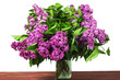 A bouquet of lilac flowers in a glass vase on a wooden table. On a white background.