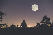 Man Enjoying The View From Hill Above City. Full Moon And Stars On The Sky.