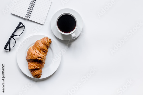 Fototapeta Businessman morning with notebook, cup of coffee and croissant on wooden table background top view mockup obraz
