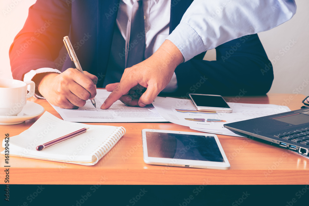Fototapeta Businessman signing a document. Tinted photo, shallow depth of field.