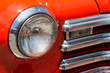 Headlight and chrome grille on an orange classic car