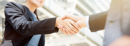 Fotomural  Businesswoman making handshake with a businessman, female leader concept