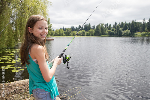 Fotografie, Obraz  Cute young girl with braces fishing on a lake