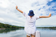 young happy woman holding up her hands joyfully in front of a beautiful lake with view of white clouds and blue sky