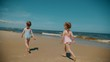 Two small and adorable girls run on the beach by the sea in summer