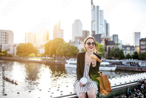 Young businesswoman having a snack with traditional Franfurt sausage and coffee Wallpaper Mural