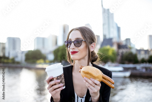 Photo Young businesswoman having a snack with traditional Franfurt sausage and coffee