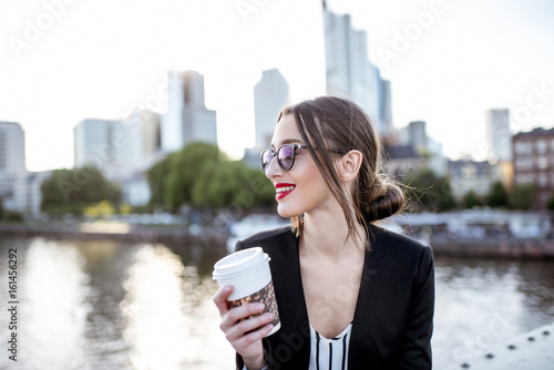 Young businesswoman having a coffee break outdoors sitting on the bridge in Fran Canvas Print