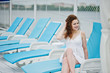 Portrait of a beautiful girl in white summer dress sitting on a lounger.
