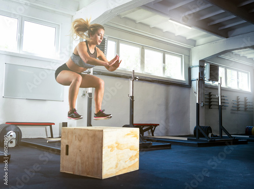 Fotografia  Fitness woman jumping on box training at the gym, crossfit exercise