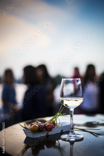 glass of white wine with gourmet food tapa snacks outside
