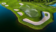 Aerial View Of Green Golf Course, Beautiful Green Golf Course With Glass Leaf Plant And Water Around.