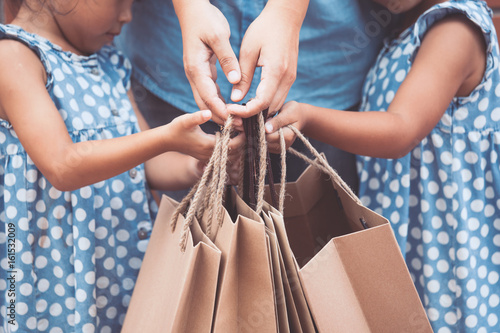 Valokuva  Kids and parent help to holding shopping bags on the in the shopping mall in vin
