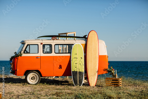 bus with a surfboard on the roof is a parked near the beach Fotobehang