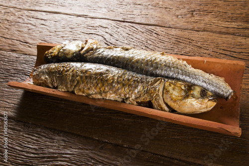 fish roasted on the tile on old wood background