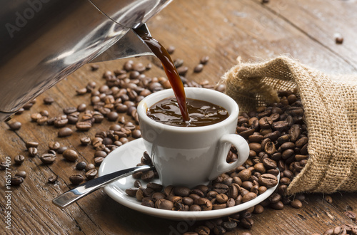 Fotografia  pouring coffee from coffeepot into white coffee cup.