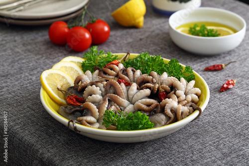 Valokuva  polpo o moscardini pesce crudo in piatto di ceramica sfondo tavolo di cucina