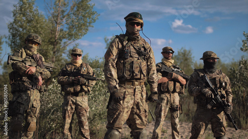 Fotografía  Group of soldiers in a camouflage and the hidden persons with weapon pose and lo