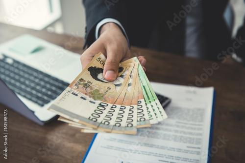 Fotomural  Businessman giving money, South Korean won banknotes
