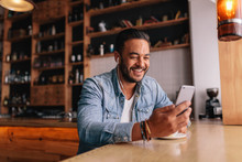 Man Having Video Chat On Smart Phone At Cafe