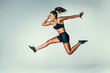 Leinwanddruck Bild - Fit young woman jumping in air