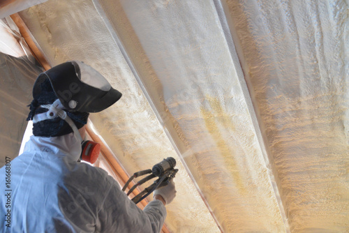 Obraz Polyurea Spraying, warming foam coating of roof, focus on wall - fototapety do salonu