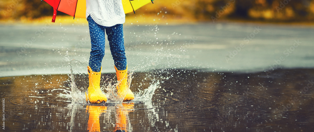 Fototapeta Feet of  child in yellow rubber boots jumping over  puddle in rain